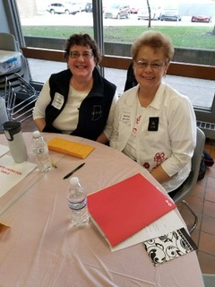 Knox sisters, Kim Gingher and Kathy Jamroz, manning a table in the White Carnation shops during the Province XII PCOT